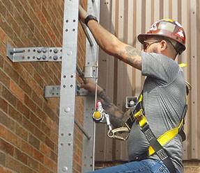 man climbing roof access ladder
